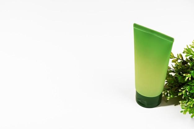 Tubo sem marca verde e planta com flores sobre fundo branco. recipiente de cosméticos em branco para creme, loção, soro. produtos cosméticos ecológicos. conceito de cosmetologia natural. estilo de maquete.