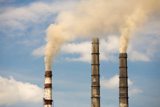 Tubos altos da central térmica com fumaça espessa