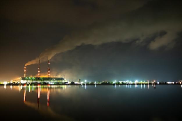 Tubos altos de usina de carvão brilhantemente iluminados com fumaça preta movendo-se para cima, poluente atmosfera à noite com reflexos na água do lago.