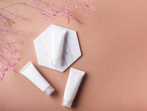 Tubos brancos de creme em uma superfície marrom e galho decorativo