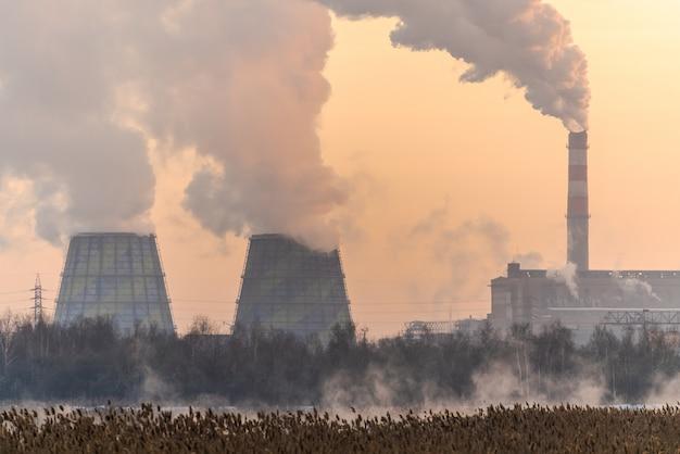 Tubos com fumaça pesada na cidade industrial no inverno, chelyabinsk, rússia