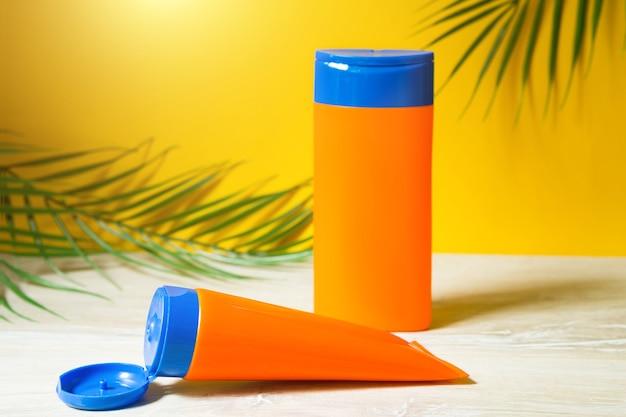 Tubos com protetores solares simulados em cima da mesa com fundo amarelo de verão. proteção uv da pele com filtro fps, shampoo e condicionador para os cabelos. um bronzeado seguro na praia, resort no mar.