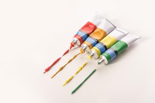 Tubos com tintas aquarela de cores diferentes, fazendo rastreamento isolado sobre fundo branco