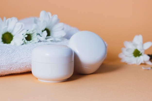 Tubos cosméticos brancos com creme facial em um fundo bege com flores brancas