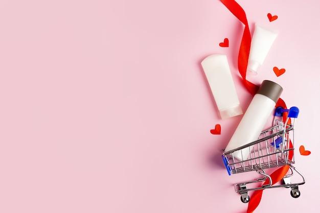 Tubos cosméticos com creme e corações vermelhos no carrinho de compras no fundo rosa. cuidados com a pele com amor, dia dos namorados