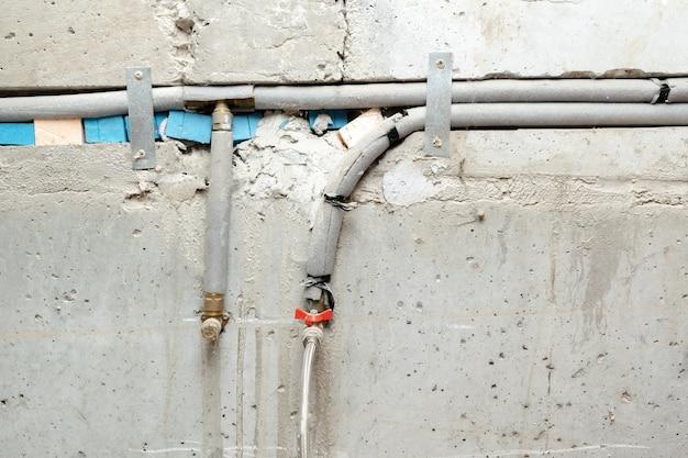 Tubos de abastecimento de água com torneiras contra parede de concreto cinza do banheiro. conceito de construção de renovação de encanamento.
