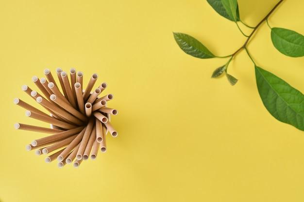 Tubos de bebida feitos de papel e amido de milho, material biodegradável e copos de papel ecológico com folhas verdes de broto em um fundo de cor amarela tendência 2021 resíduos zero e conceito livre de plástico. vista do topo