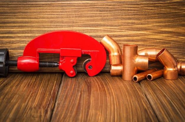 Tubos de cobre e um corta-tubos vermelho com conectores para reparos de encanamento em closeup de tábuas de madeira vintage