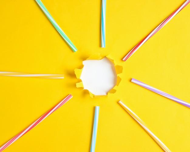 Tubos de cocktail em uma mesa de papel amarelo com um buraco rasgado.