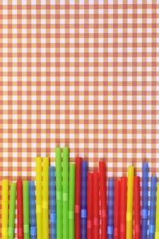 Tubos de coquetel coloridos repousam sobre um fundo de cor brilhante