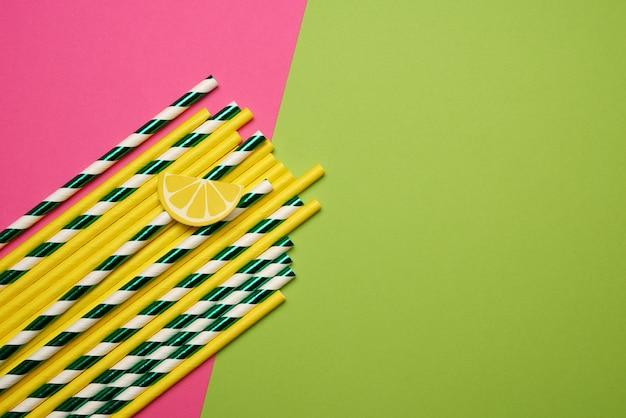 Tubos de coquetel multicoloridos de papel em fundo verde rosa, rejeição de plástico, desperdício zero