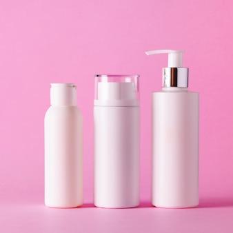 Tubos de cosméticos brancos em fundo rosa com espaço de cópia