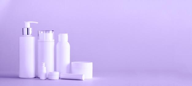 Tubos de cosméticos brancos sobre fundo de cor violeta na moda
