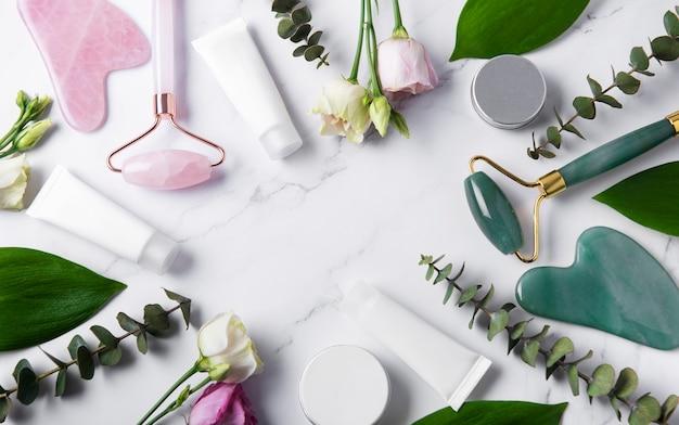 Tubos de creme de produtos cosméticos, rolo facial e eucalipto em mesa de mármore. vista do topo. spa relax, tratamento corporal, spa, conceito de cuidados com a pele.