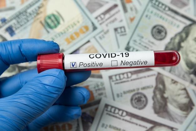 Tubos de ensaio com amostra de sangue em coronavírus. fundo de dinheiro. quanto custa a análise de custos no covid-19