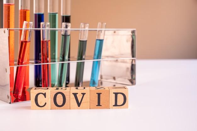 Tubos de ensaio contendo medicamentos anti-retrovirais ou amostras de sangue para detectar coronavírus e texto escrito em caixa de madeira