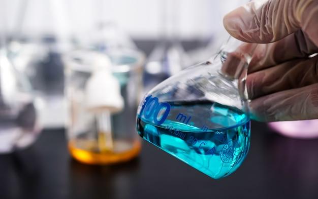 Tubos de ensaio de laboratório com amostras cientistas seguram um copo com um líquido azul nas mãos