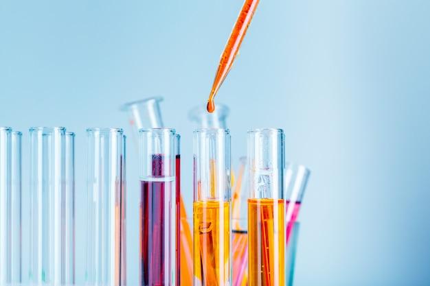 Tubos de ensaio de laboratório com líquidos vermelhos e amarelos na luz azul