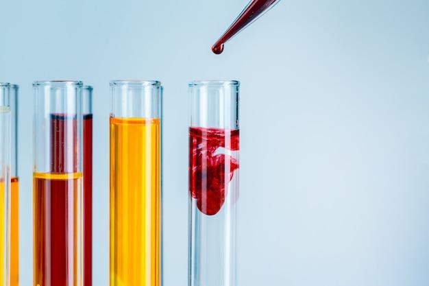 Tubos de ensaio de laboratório com líquidos vermelhos e amarelos sobre fundo azul claro
