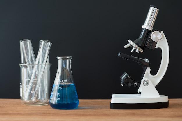 Tubos de ensaio de laboratório de ciência e microscópio branco na mesa de madeira com fundo preto