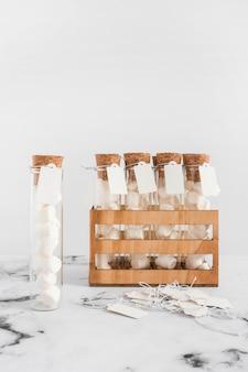 Tubos de ensaio de marshmallow com tag na parte superior de mármore contra o fundo branco