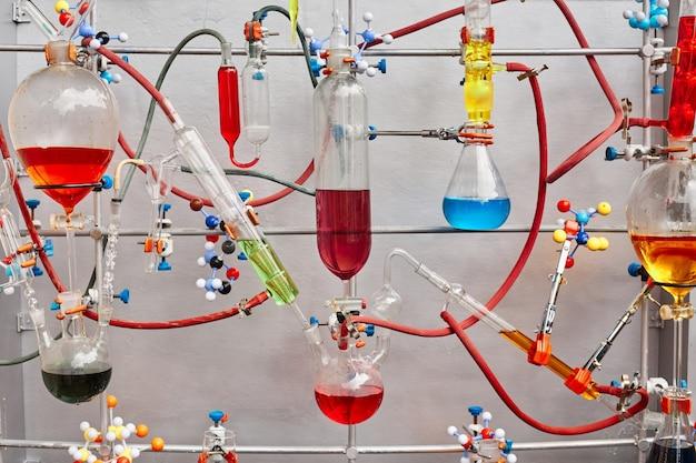 Tubos de ensaio de vidro com líquido viscoso colorido isolados sobre superfície cinza em laboratório químico