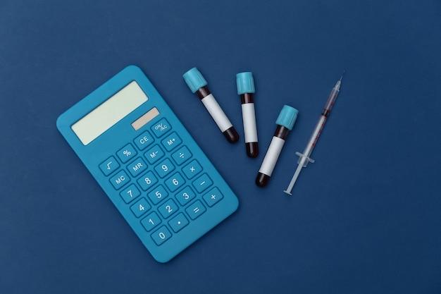 Tubos de ensaio médico com sangue, seringa e calculadora em um fundo azul clássico. vista do topo