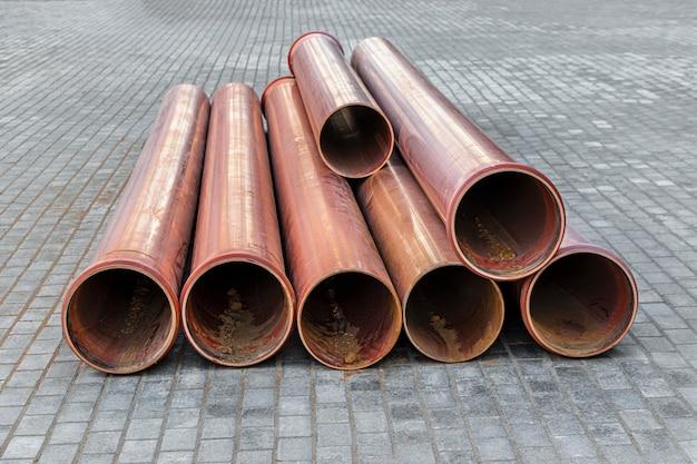 Tubos de esgoto laranja mentem em um canteiro de obras. preparação de terraplenagem para instalação de duto subterrâneo.