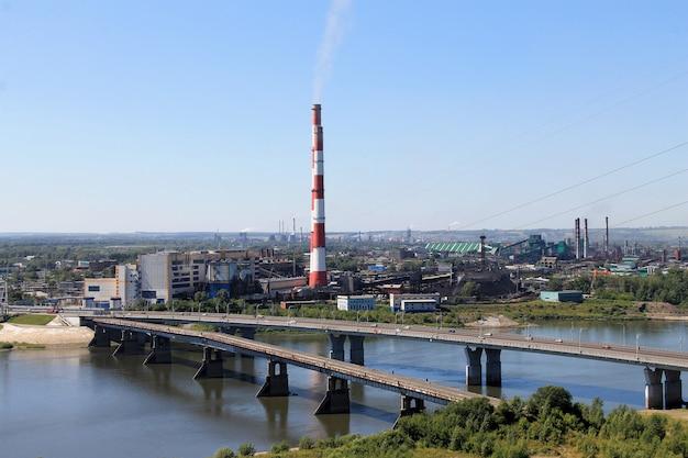 Tubos de fábrica no fundo de uma cidade grande, um rio e uma ponte sobre o rio