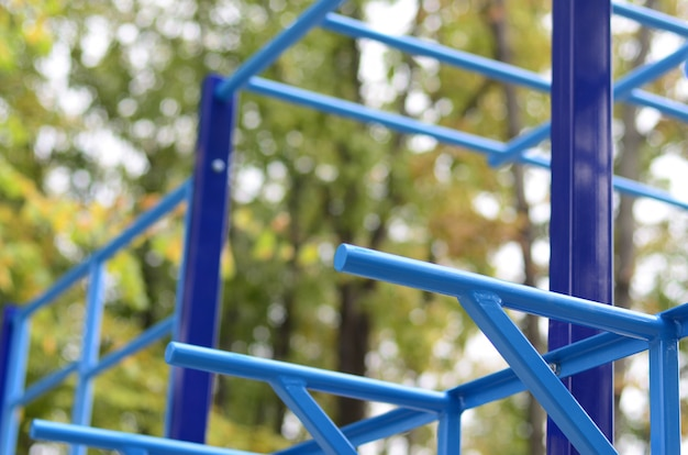Tubos de metal azul e barras transversais contra um campo de esportes de rua para treinamento em atletismo