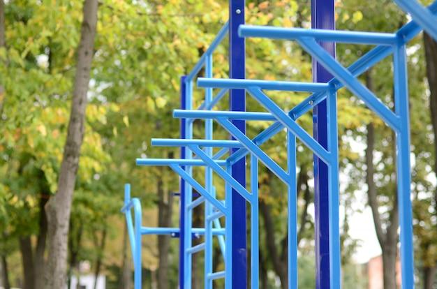 Tubos de metal azul e barras transversais contra um campo de esportes de rua