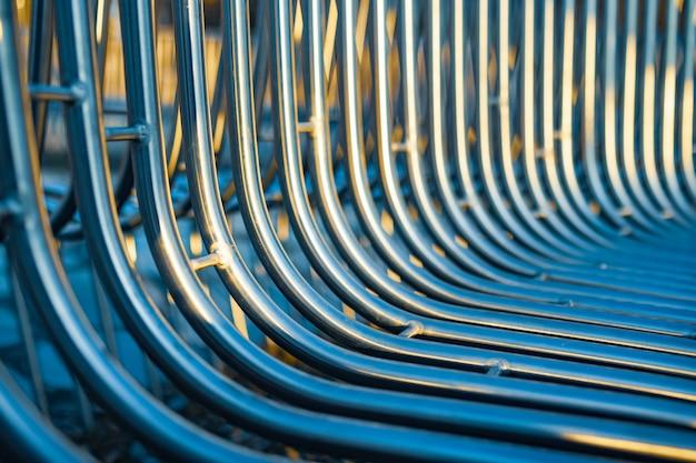 Tubos de metal em banco de rua em close-up dispostos paralelamente