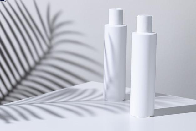 Tubos de plástico para cuidados da pele em um fundo de sombra de planta tropical com espaço de cópia