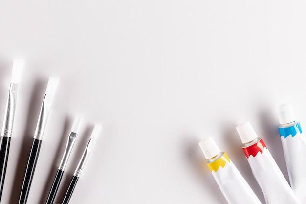 Tubos de tinta e pincéis na mesa branca