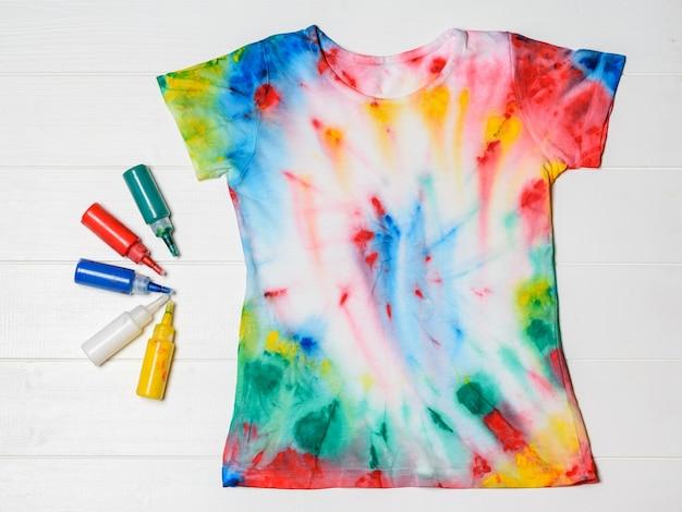 Tubos de tinta para roupas e camiseta no estilo tie dye em uma mesa branca