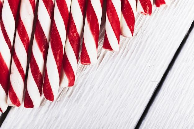 Tubos listrados de vermelhos e brancos na placa de madeira