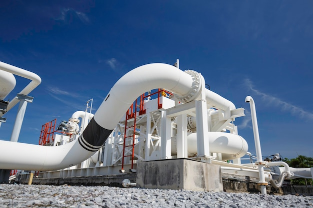 Tubos longos de aço e cotovelo de tubo na fábrica de petróleo da estação durante a refinaria indústria petroquímica em destilaria de gás.