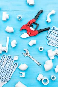 Tubos plásticos para o sistema de água, ferramentas de corte de tubos, chave, cantos, suportes, torneiras, adaptadores e luvas de trabalho em uma superfície azul clara. vista do topo.