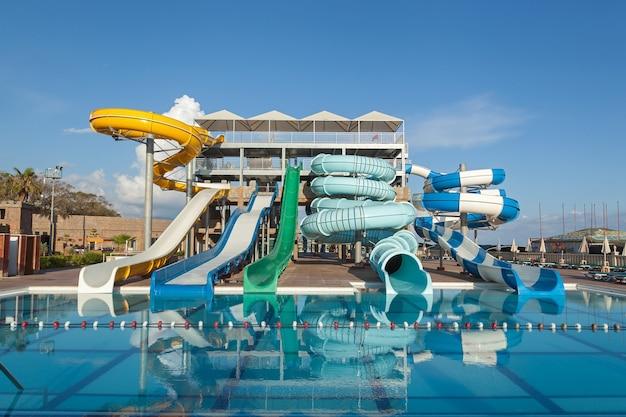Tubos redondos multicoloridos em um parque aquático perto da piscina