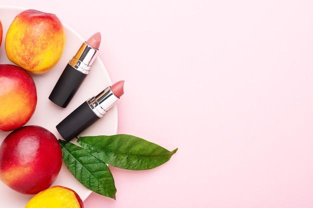 Tubos vermelhos de batom com nectarinas maduras suculentas brilhantes na copmposition de carrinho-de-rosa, pêssegos em um fundo rosa. frutas de verão, acessórios de maquiagem feminina. cosméticos orgânicos, vista superior, copie o espaço.