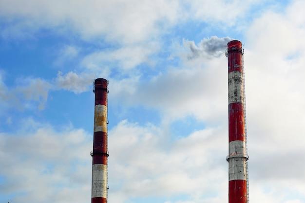 Tubos vermelhos e brancos com fumaça em um fundo de céu azul com nuvens