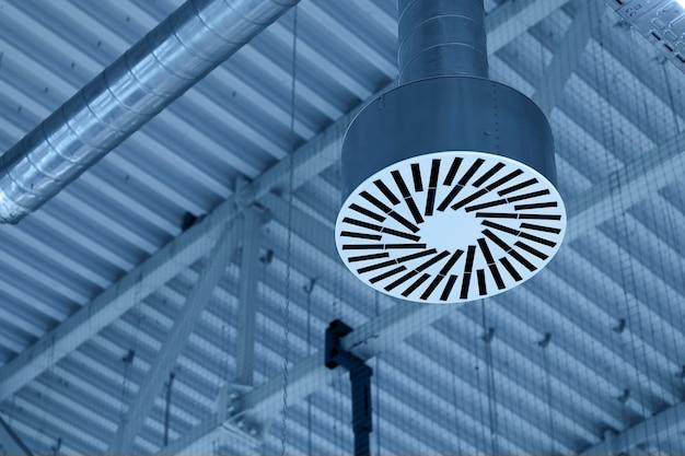 Tubulação de abastecimento e sistema de ventilação exaustora no teto de sala comercial ou armazém.