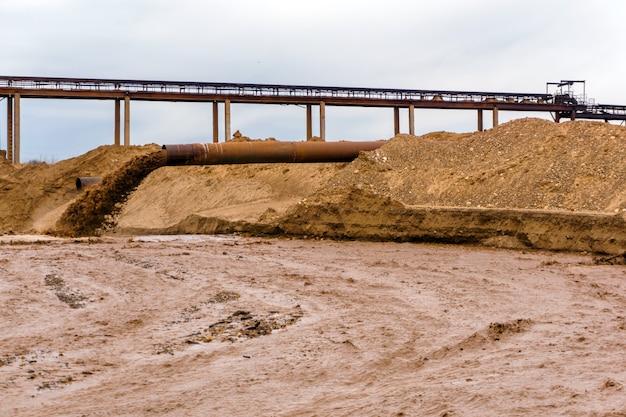 Tubulação enferrujada na margem do rio, de onde flui o esgoto, lama suja de areia