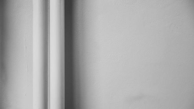 Tubulação plástica branca na parede do cimento branco com sombra.