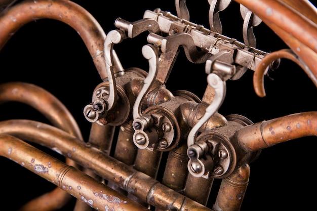 Tubulações de bronze vintage, válvula, trompa de elementos mecânicos chave sobre fundo preto isolado.