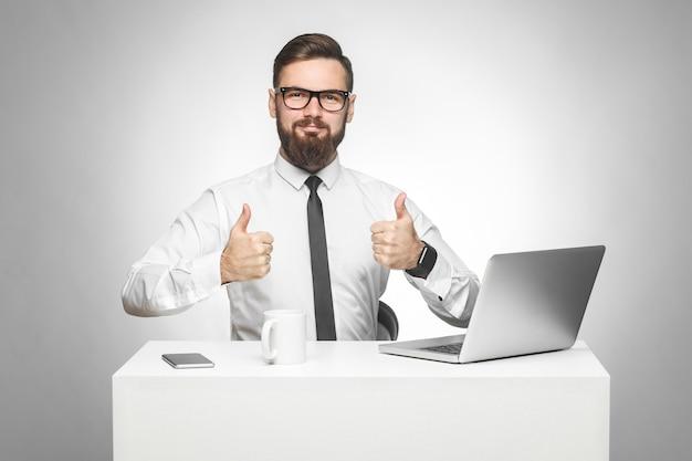 Tudo certo! retrato de um jovem empresário barbudo satisfeito bonito de camisa branca e gravata preta está sentado no escritório e trabalhando no laptop com um sorriso e mostrando o polegar, olhando para a câmera