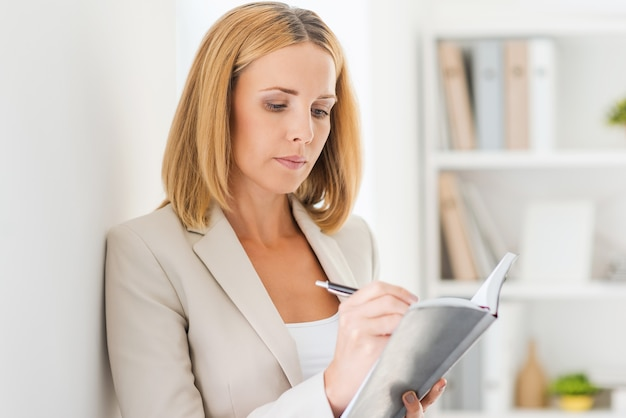 Tudo deve estar em ordem. mulher de negócios madura confiante escrevendo em um bloco de notas