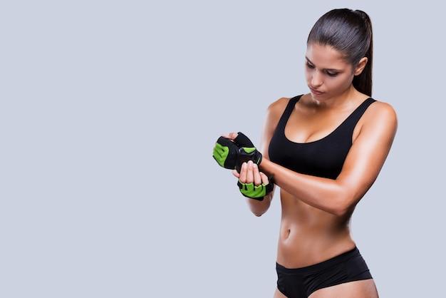 Tudo deve ser perfeito. mulher jovem e bonita desportiva com corpo perfeito ajustando suas luvas esportivas em pé contra um fundo cinza