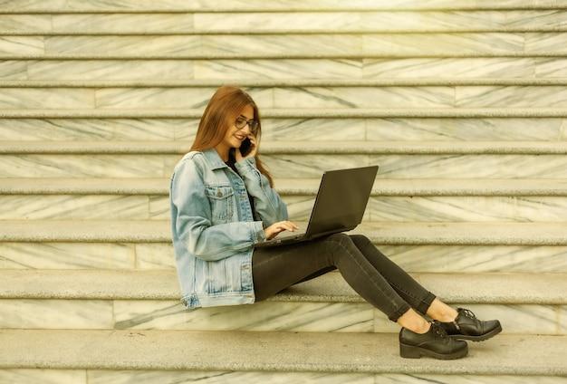 Tudo em funcionamento. jovem mulher elegante em uma jaqueta jeans e óculos usa um laptop e falando ao telefone enquanto está sentado na escada na cidade. trabalho remoto.