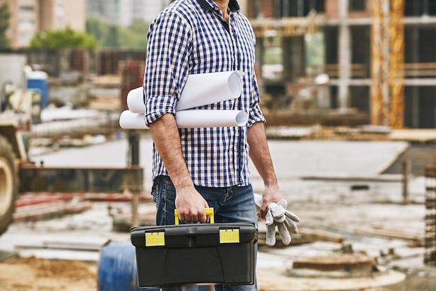 Tudo o que eu preciso para trabalhar imagem recortada de um construtor segurando luvas protetoras de caixa de ferramentas